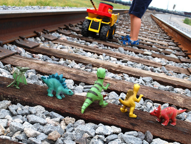 Playing with dinosaurs along train tracks