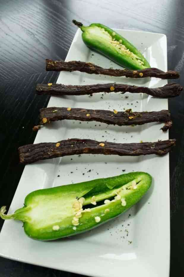 South Texas jalapeno jerky on white dish with fresh jalapenos cut in half