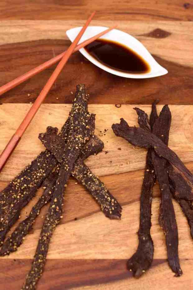 Jimmy's Teriyaki Deer jerky on a cutting board with teriyaki sauce and chopsticks.