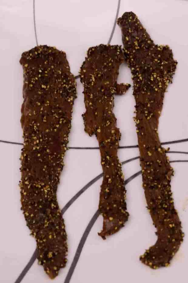 Deer jerky pieces topped with black pepper on plate