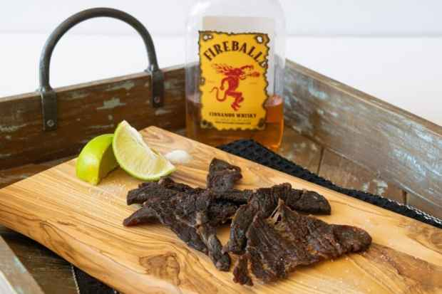 Fireball whisky bottle behind beef jerky on cutting board with two lime wedges
