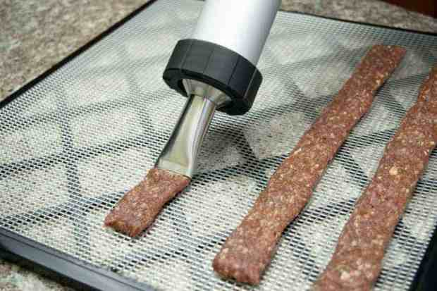shooting ground jerky strips onto dehydrator tray with jerky cannon