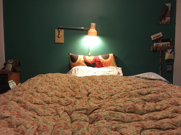picture of my bed taken from the foot of it, featuring a comfy looking comforter and some groovy looking pillowcases.