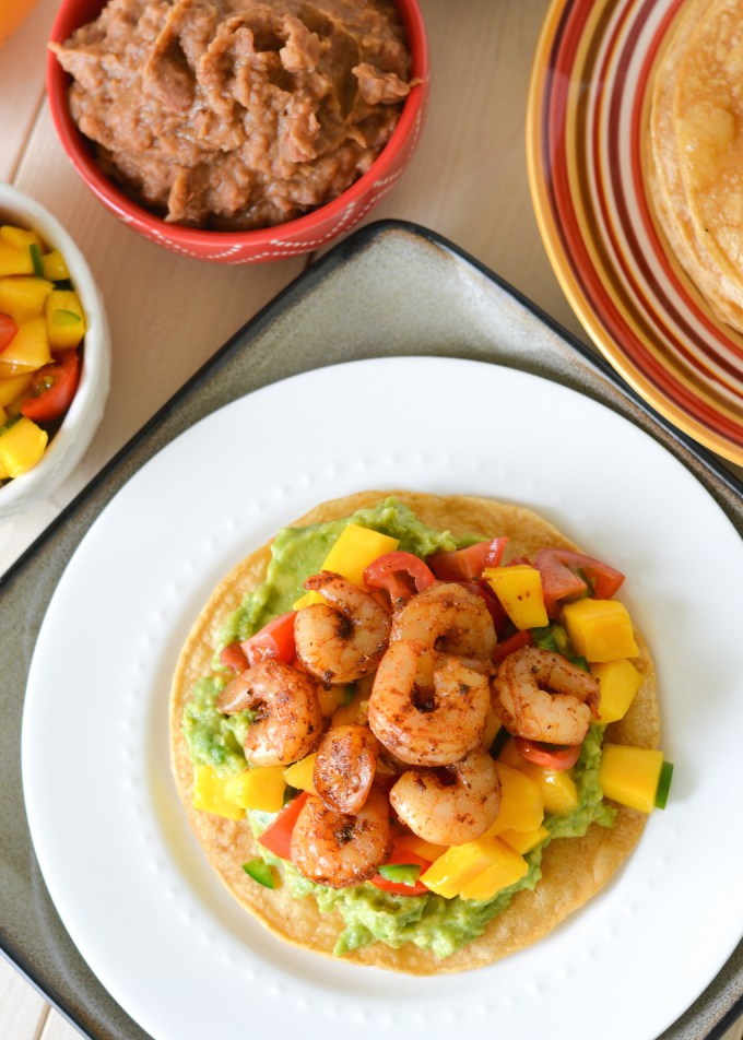 These Mango Shrimp Tostadas are quick and easy, ready in less than 30 minutes. Crunchy tortillas are topped with smashed avocado, mango salsa and spicy shrimp!