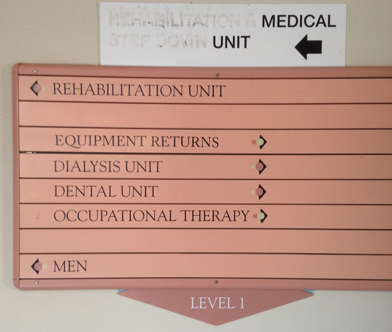 Hospital signage pointing in the direction of the rehabilitation unit, equipment returns, dialysis unit, dental unit, occupational therapy, and men. I assume the last is incomplete somehow.