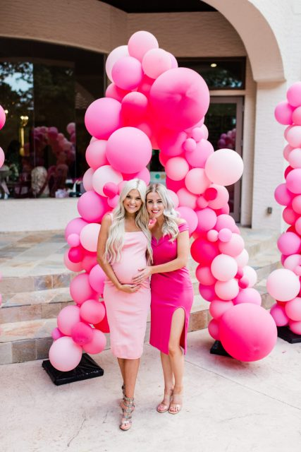 Cute Pink Baby Shower Ideas featured by top Houston lifestyle blogger and expecting mom, Jessica Crum. | Pink Baby Shower by popular Houston motherhood blogger, Jessica Crum: image of Jessica Crum and a friend standing in front of a Lushra pink balloon baby sign.