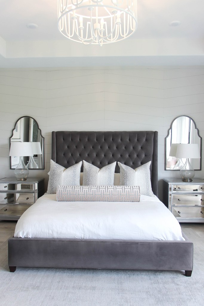 Arhaus bed | Master Bedroom Ideas by popular Houston life and style blogger, Jessica Crum: image of a master bedroom decorated with a Arhaus devereaux tufted bed, Arhaus lamp, Arhaus reese three drawer dresser, jackson handwoven rug, Arhaus italian linen hemstitch duvet cover, Etsy ShopLittleDesignCO Antelope Linen Print grey print pillow cover, Etsy ShopLittleDesignCo The Bolster : Grecian Cut Velvet, and Wayfair Chandler 6 - Light Unique / Statement Drum Chandelier.