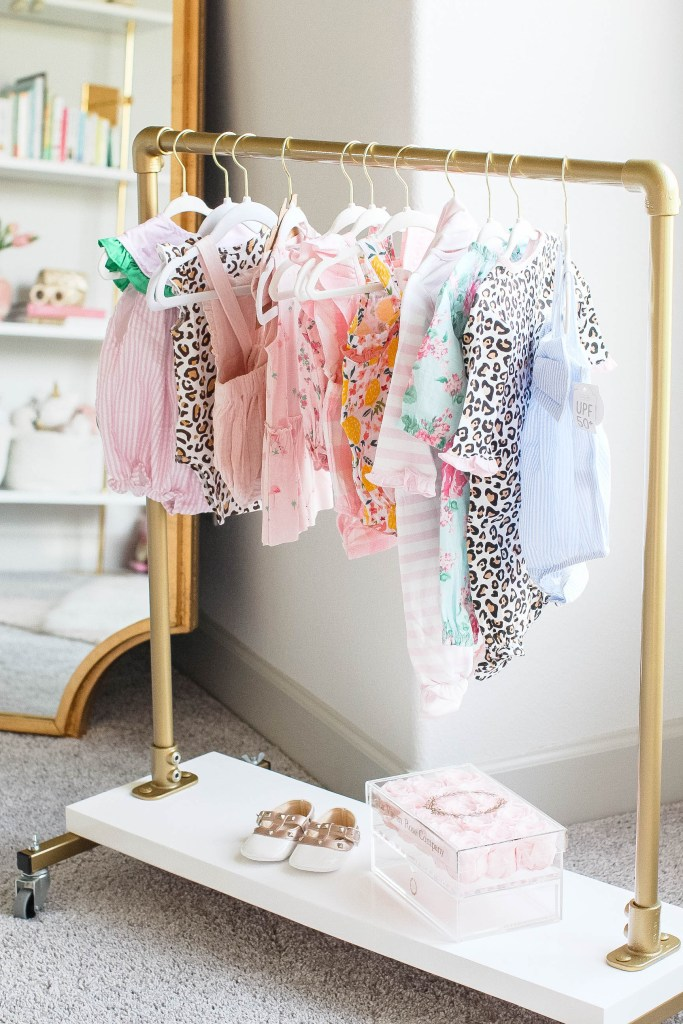 Girl Nursery by popular Houston motherhood blogger, Jessica Crum: image of a nursery decorated with a Boutique Rugs Bellaghy Mirror, Etsy Childrens standard rack, La Vie En Rose Le Medium rose box, Mud Pie clothes and Angel dear clothes.