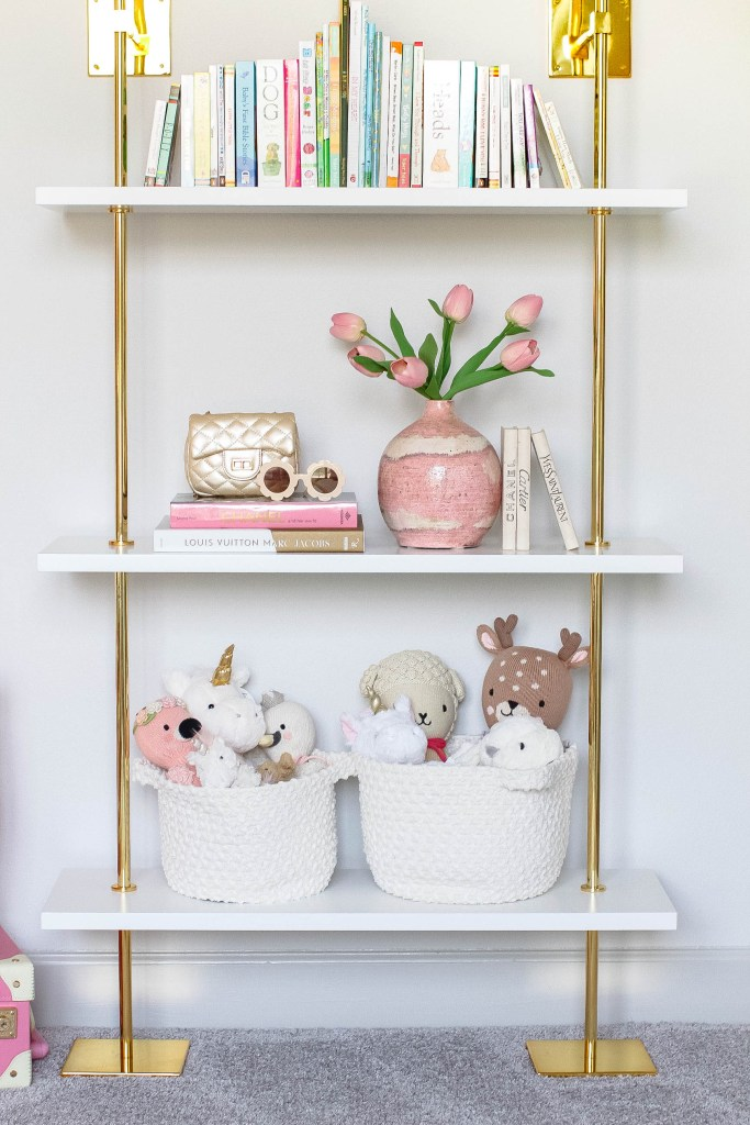 Girl Nursery by popular Houston motherhood blogger, Jessica Crum: image of a nursery decorated with a gold and white book case, pink suitcase, Cuddle and Kind stuffed animals and a Mud Pie Princess flamingo in Mud Pie white storage bins,  Dillard's girls quilted crossbody handbag, white blessing beads, and a framed Ladie Katie new mom art print.