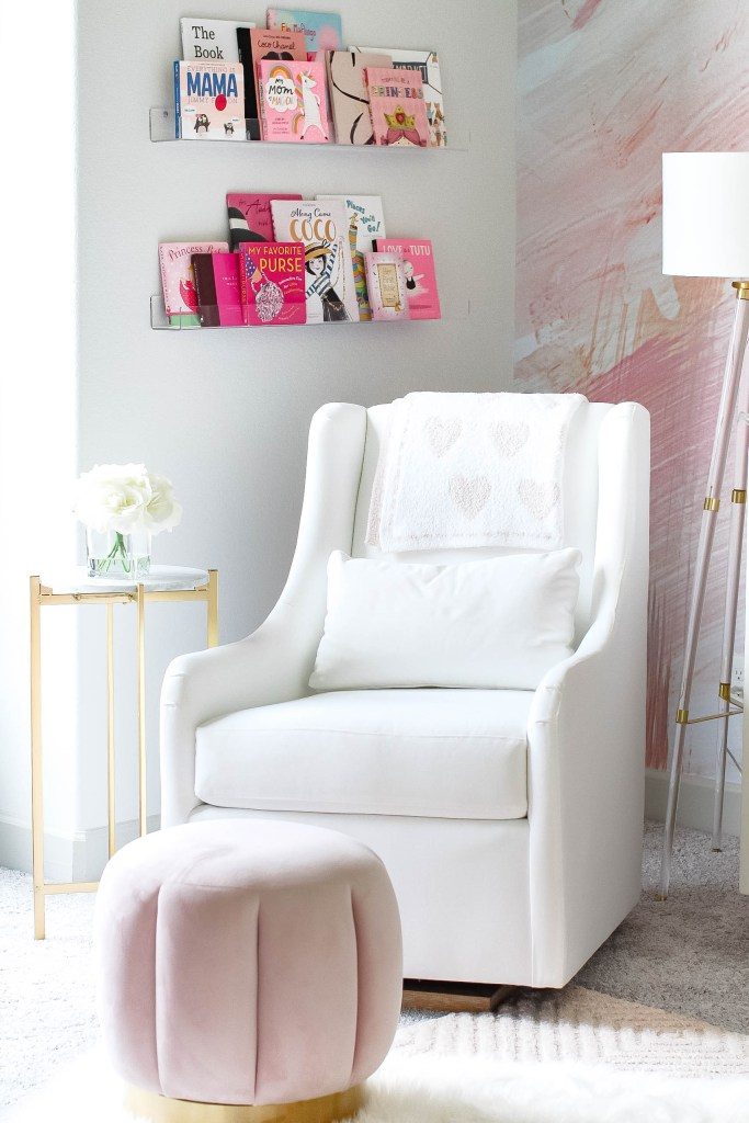 Girl Nursery by popular Houston motherhood blogger, Jessica Crum: image of a nursery decorated with Wall Blush The Nora Mural, Barefoot Dreams Cozychic Dream Receiving Blanket, Target tufted ottoman, acrylic floor lamp, Pottery Barn Kids Frye rug, white glider chair, and acrylic shelves filled with various children's books.