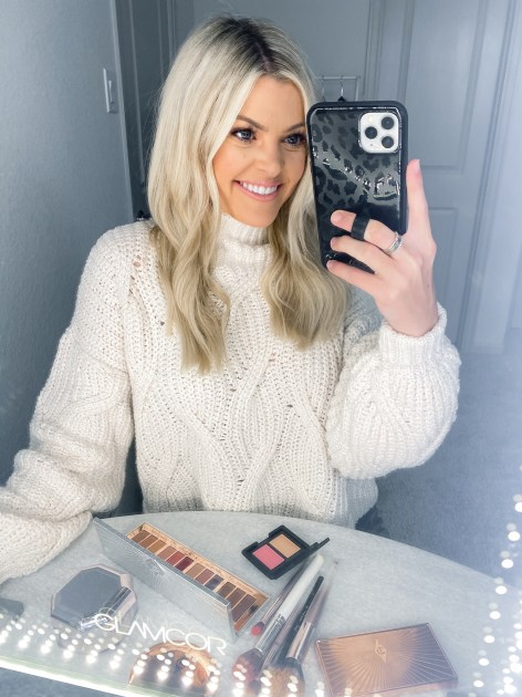 Pink Makeup by popular Houston beauty blogger, Jessica Crum: image of Jessica Crum taking a selfie in her bathroom mirror while standing in front of some makeup.