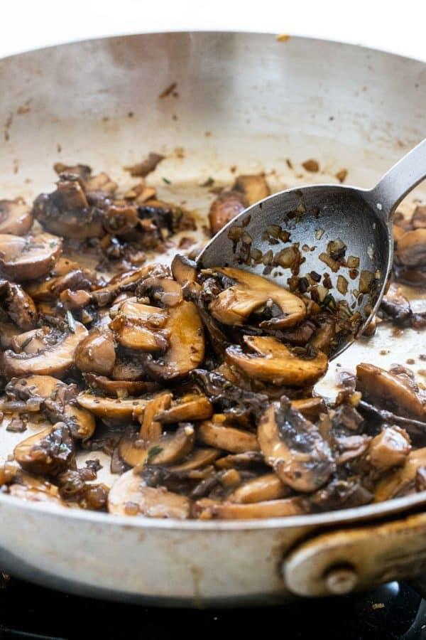 sliced mushrooms sauteing in a pan