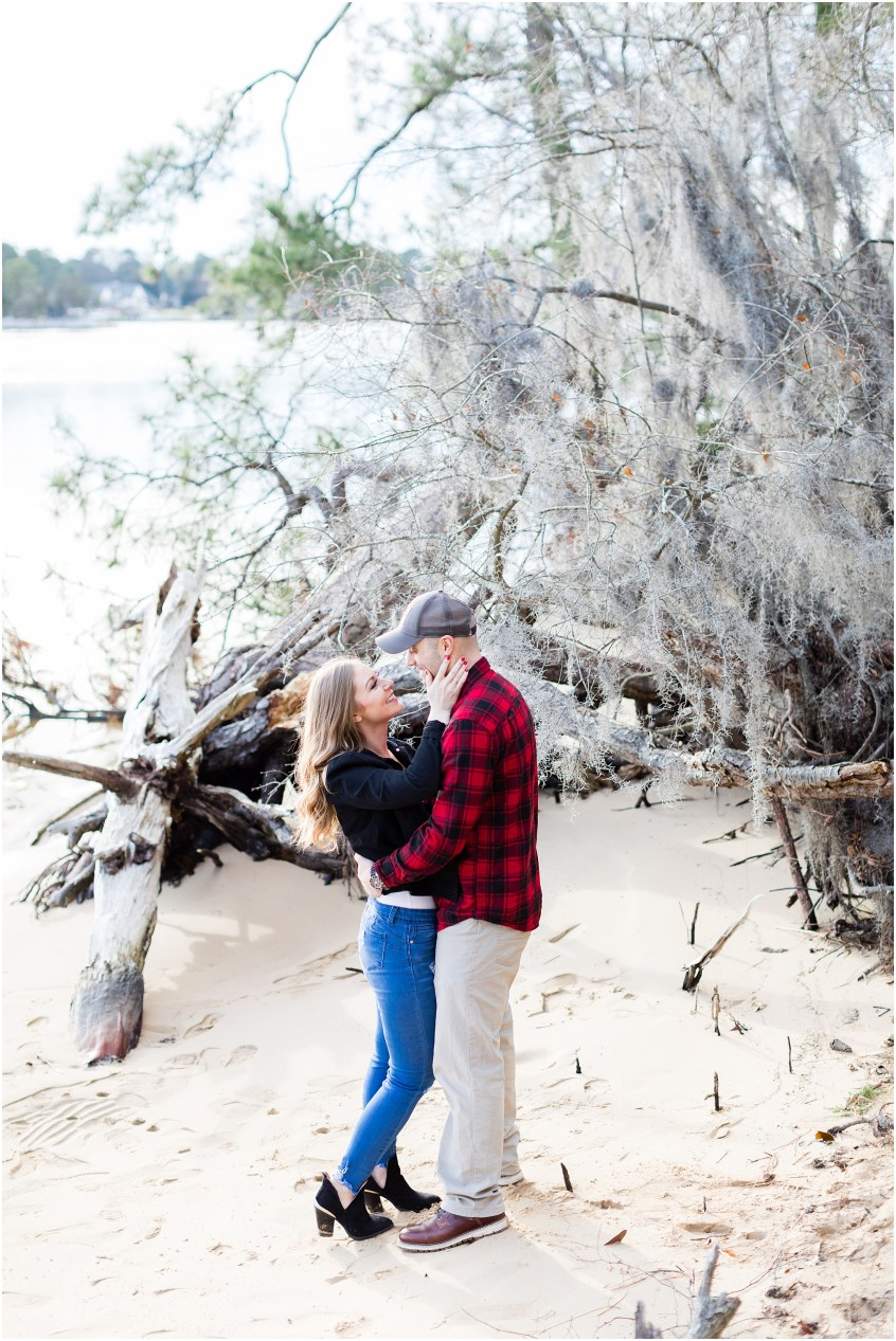 Virginia state park engagement, first landing state park engagement photography, couple on the beach with driftwood, spanish moss