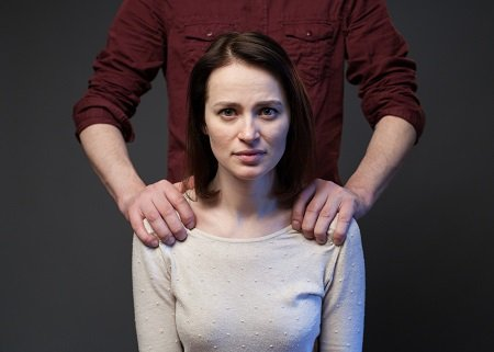 image of abused woman being held down by abuser's hands