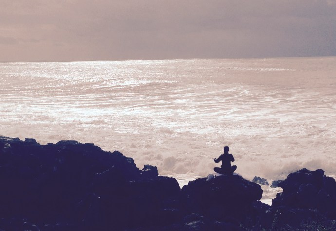 a women sitting on rock by the sea
