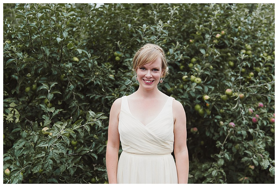 portrait of bride with Ivory dress and mermaid braid in front of apple orchard at Red Barn Studios, Chehalis, WA