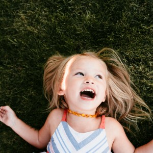 young girl laughing on grass by lifestyle Seattle photographer Jessica Uhler