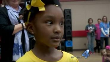 Dziewczynka rozdaje dzieciom żółte plecaki. Ich zawartość wywołuje na twarzach najmłodszych szeroki uśmiech!