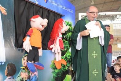 Os bonecos Inacinho e a Lourdinha interagem com o celebrante, padre Eugênio Pacelli Correia Aguiar, e com as crianças