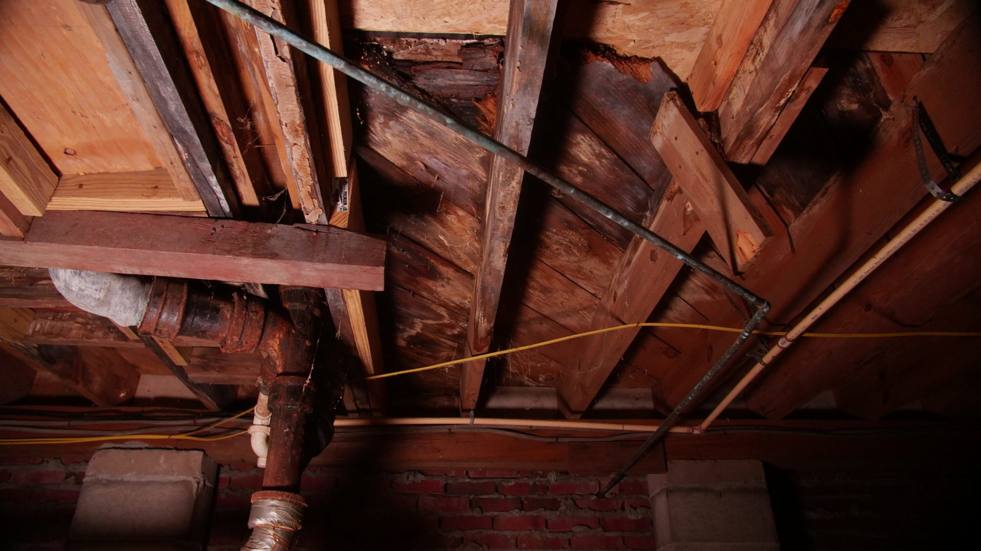 rusty pipes with rotting wood floor joists