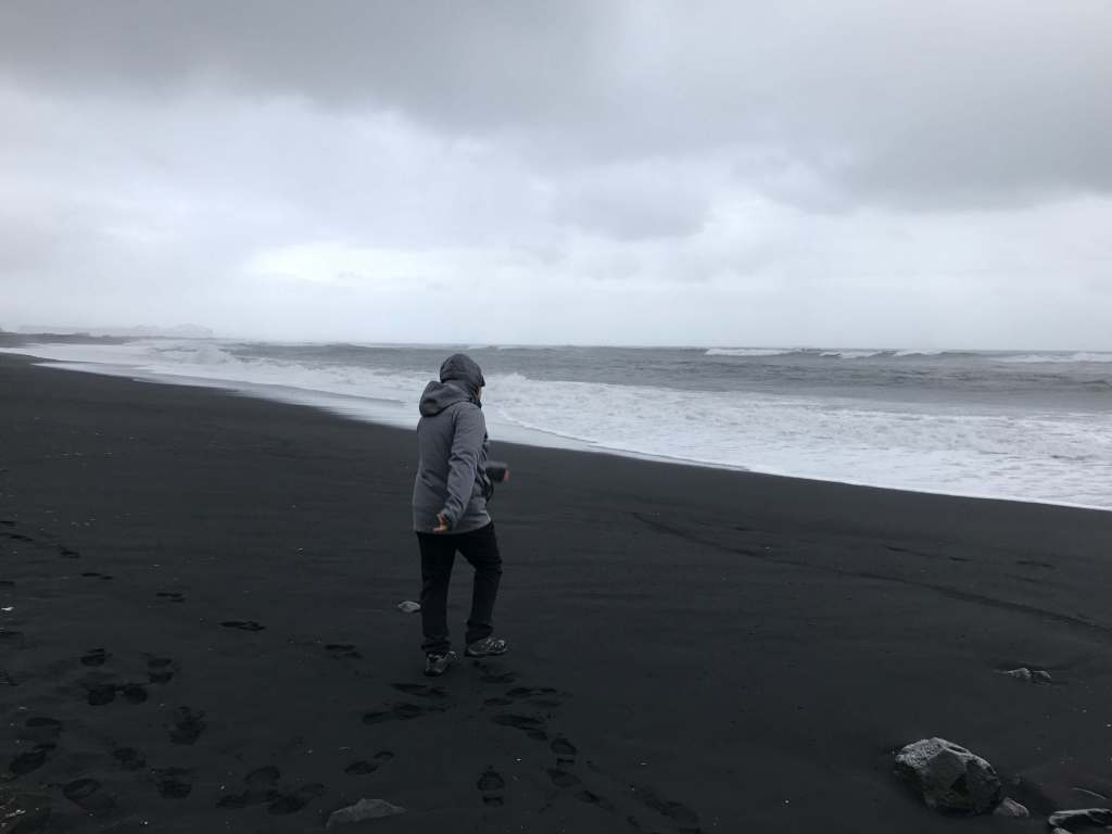 Man walking on black sand by the water