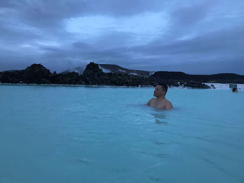 Man relaxing in blue water with mountains in background