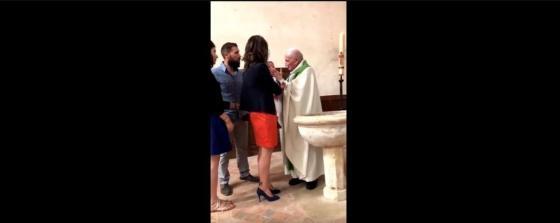 Un prêtre frappe un bébé pendant son baptême