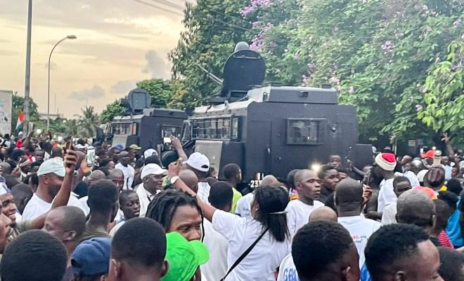 Des blindés des forces de l'ordre au milieu de la foule de partisans de Laurent Gbagbo, près du QG du FPI à Attoban, le 17 juin 2021, au moment de l'arrivée de l'ancien président ivoirien.
