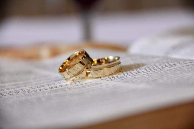 2 yellow gold rings on a book