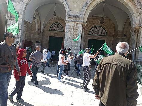 Partidarios de Hamas que marcha en el Monte del Templo, agitando banderas de Hamas.