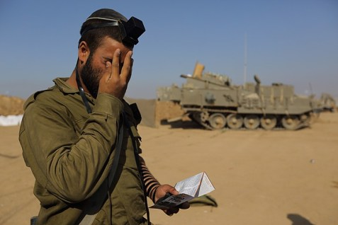 An Israeli soldier prays at an IDF staging area near the Israeli border with Gaza, on July 31, 2014.