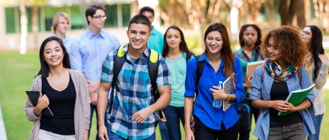 Teenagers or young adults walking outdoors on school campus. Hispanic, Caucasian, and African American students are smiling while walking together to class. They are wearing trendy casual clothing and backpacks, and are carrying school books.