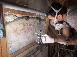 Conservators inspecting the wall paintings