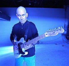 Jim standing playing guitar