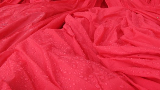 Rain coverd red nylon fabric during installation of inflatable sculpture on Governors Island