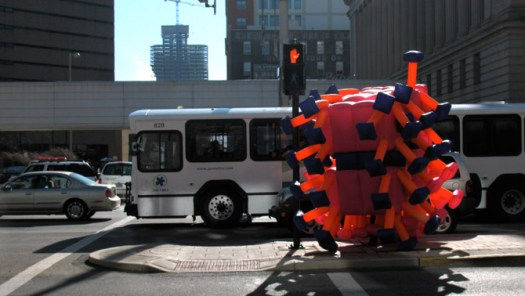 Jimmy Kuehnle standing on the median of a road in his inflatable suit in Cincinnati