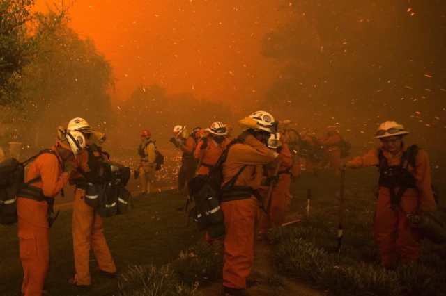 Inmate handcrew firefighters shield themselves from embers and heavy smoke as flames close in on houses at the Sand Fire on July 23 2016 near Santa Clarita, California. Fueled by temperatures reaching about 108 degrees fahrenheit, the wildfire began yesterday has grown to 11,000 acres. / AFP / DAVID MCNEW (Photo credit should read DAVID MCNEW/AFP/Getty Images)