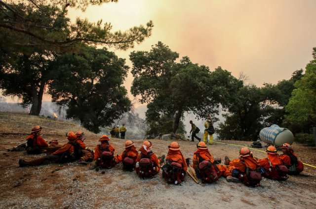 Members of hand crew rest on a hillside near Placenta Canyon Road as a wildfire burns in Santa Clarita, Calif., Sunday, July 24, 2016. Thousands of homes remained evacuated Sunday as two massive wildfires raged in tinder-dry California hills and canyons. (AP Photo/Ringo H.W. Chiu)