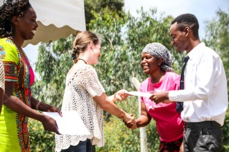 John's mother shakes hands with Jitegemee Executive Director, Verity Norman-Tichawangana and new Country Director Jennifer Katiwa at Jitegemee's Children's Day on 14 December 2017, after John received his certificate.