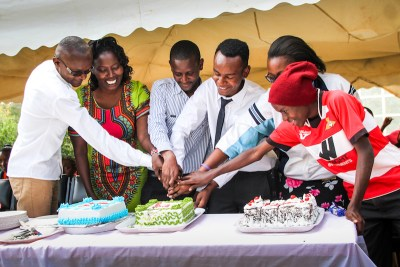 John's friends and family help him cut a celebratory graduation cake at Jitegemee Children's Day.
