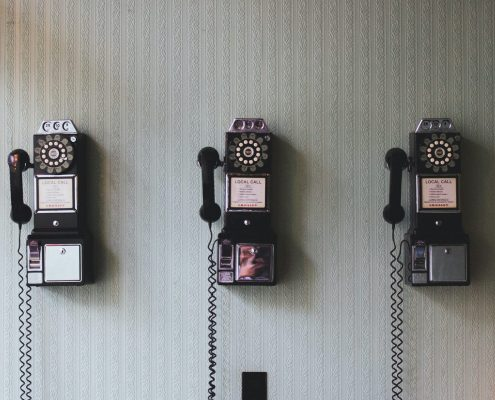 3 vintage telephone on the wall Photo by Pavan Trikutam on Unsplash