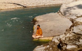 Young Babaji in Saffron meditating at a river