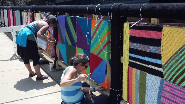 Volunteers installing hand-made knit and crochet panels