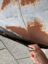 Visible rusting below the shingles of a commercial shingle roof