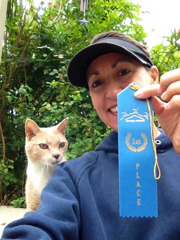 Photo of Joan Jakel holding 1st place ribbon for 1/2 marathon trail race she ran at Huddart Park