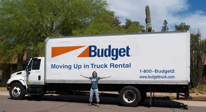 A photo of Joan Jakel in front of the Budget Truck she drove from AZ to Napa