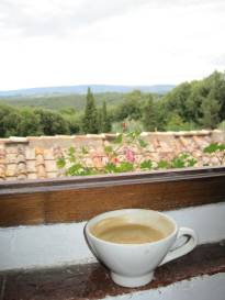 a photo of a latte on a windowsill overlooking the Italian countryside which was a reward for Creating my Inspired Life and a lesson in the 21 day program to Create Your Inspired Life
