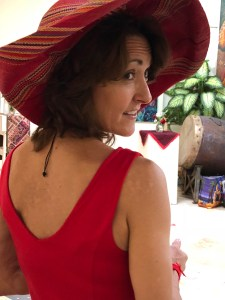 an image of Joan Jakel looking over her shoulder and she's wearing a red hat and dress