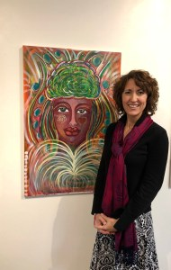 an image of Joan Jakel standing next to her painting the Muse