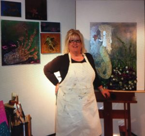 Sheryl Marshall standing next to her easel with a painting on it
